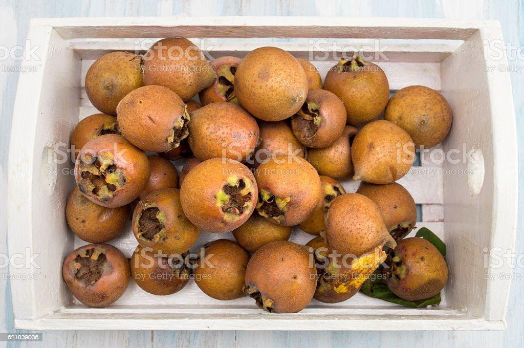Medlar fruit in a wooden box stock photo