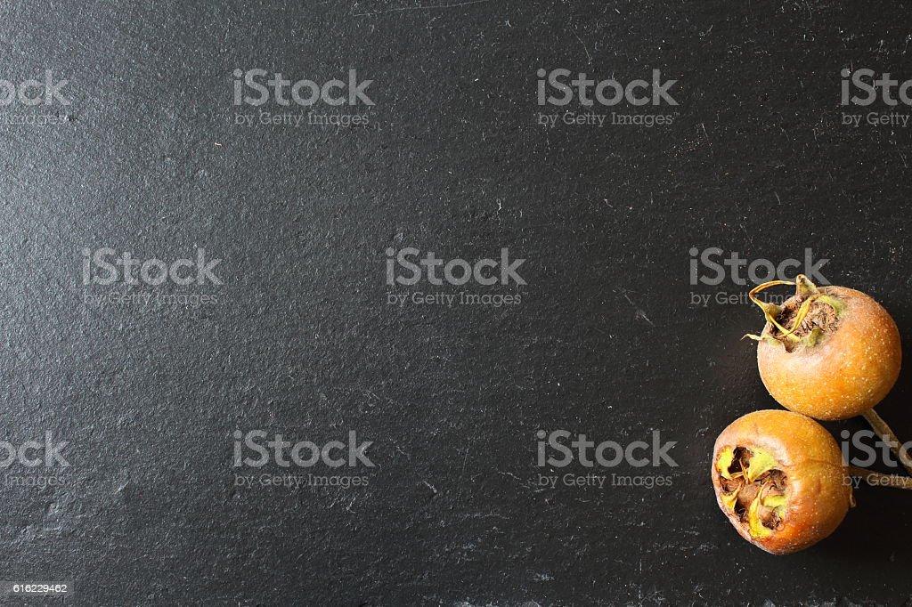 medlar fruits on a slate plate stock photo