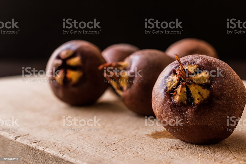 Medlar Fruits on a wooden surface. stock photo