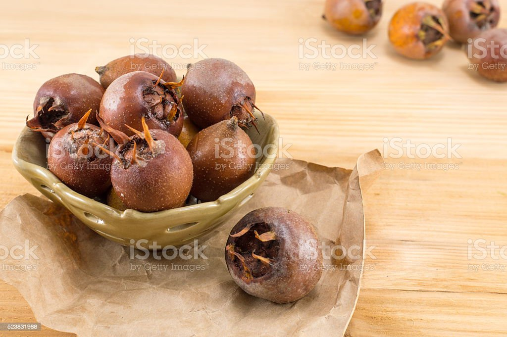 Medlars on an old wooden table stock photo