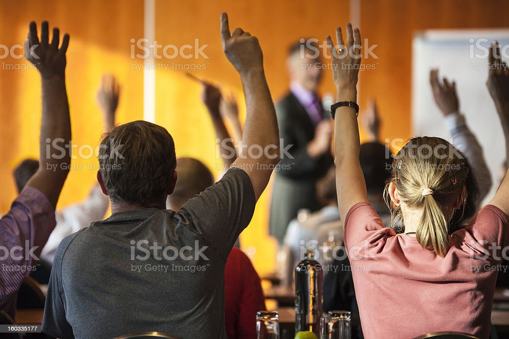 Meeting attendees with raised hands in foreground royalty-free stock photo