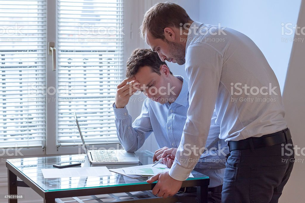 Meeting of two businessmen with laptop and charts stock photo