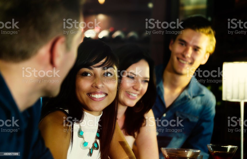 Meeting up: four young people at bar, drinking and flirting stock photo