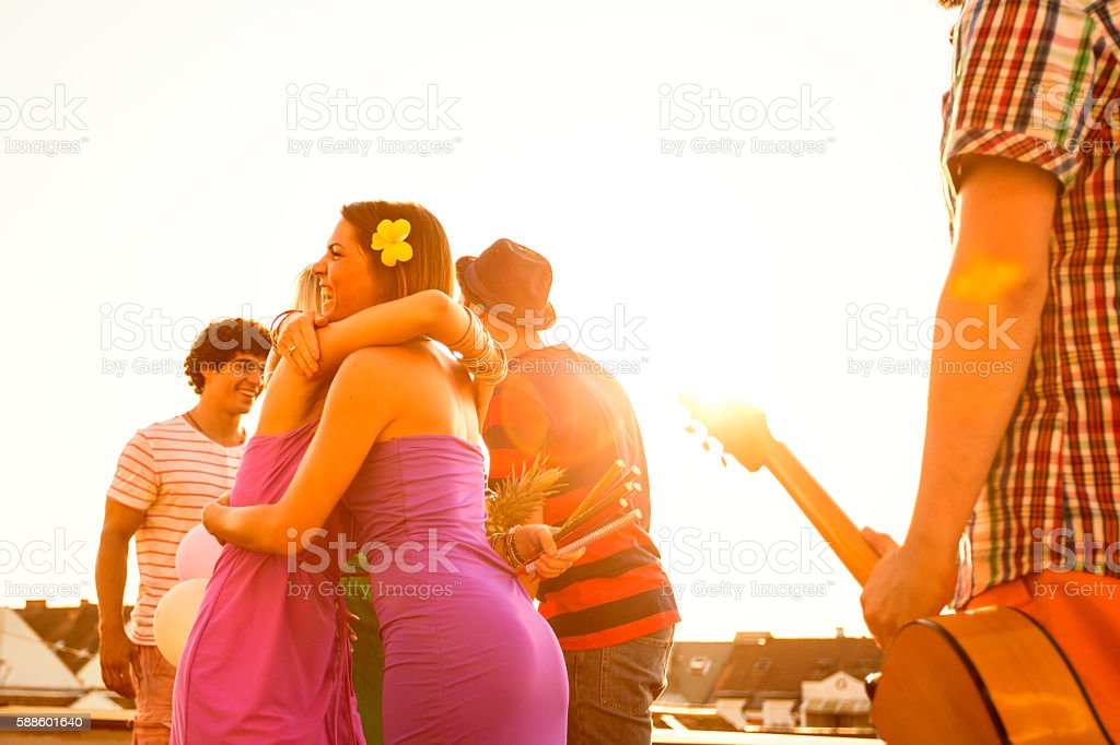 Meeting with friends at rooftop party stock photo