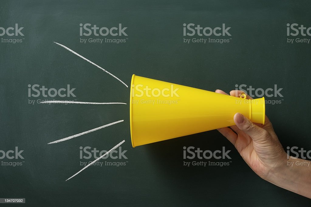 Megaphone with hand in front of blackboard royalty-free stock photo