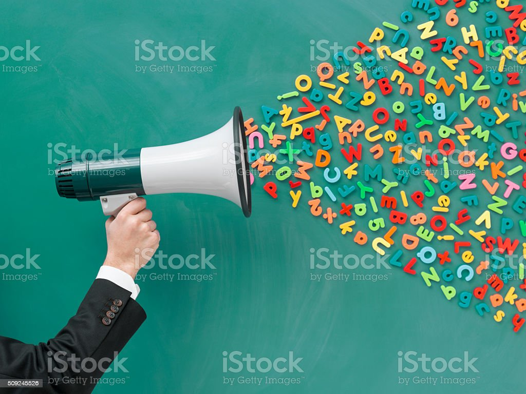 Megaphone with letters and numbers on blackboard for communication pollution stock photo