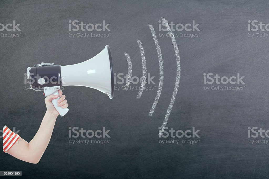 Megaphone with woman hand on blackboard stock photo