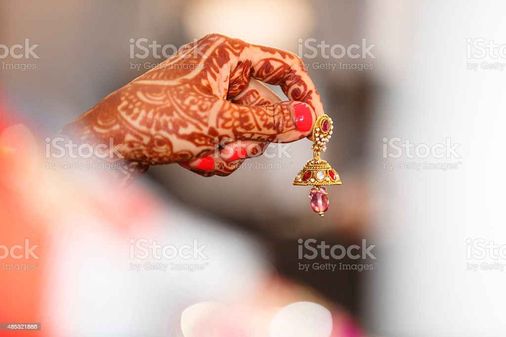 Mehendi adorned Bride's hand holding an earring stock photo