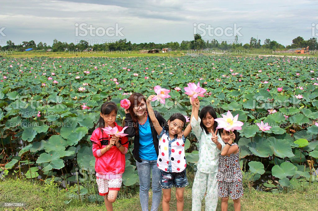 Mekong Delta kids playing with pinky lotus stock photo