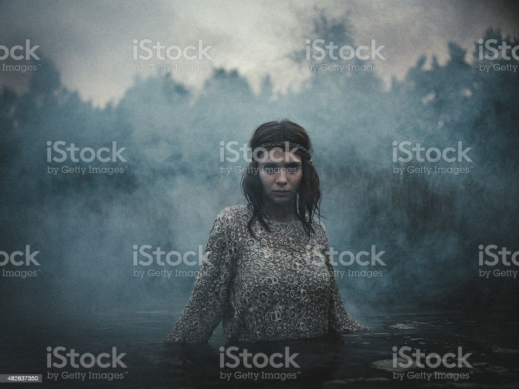 Melancholy girl standing in a lake surrounded by smoke stock photo