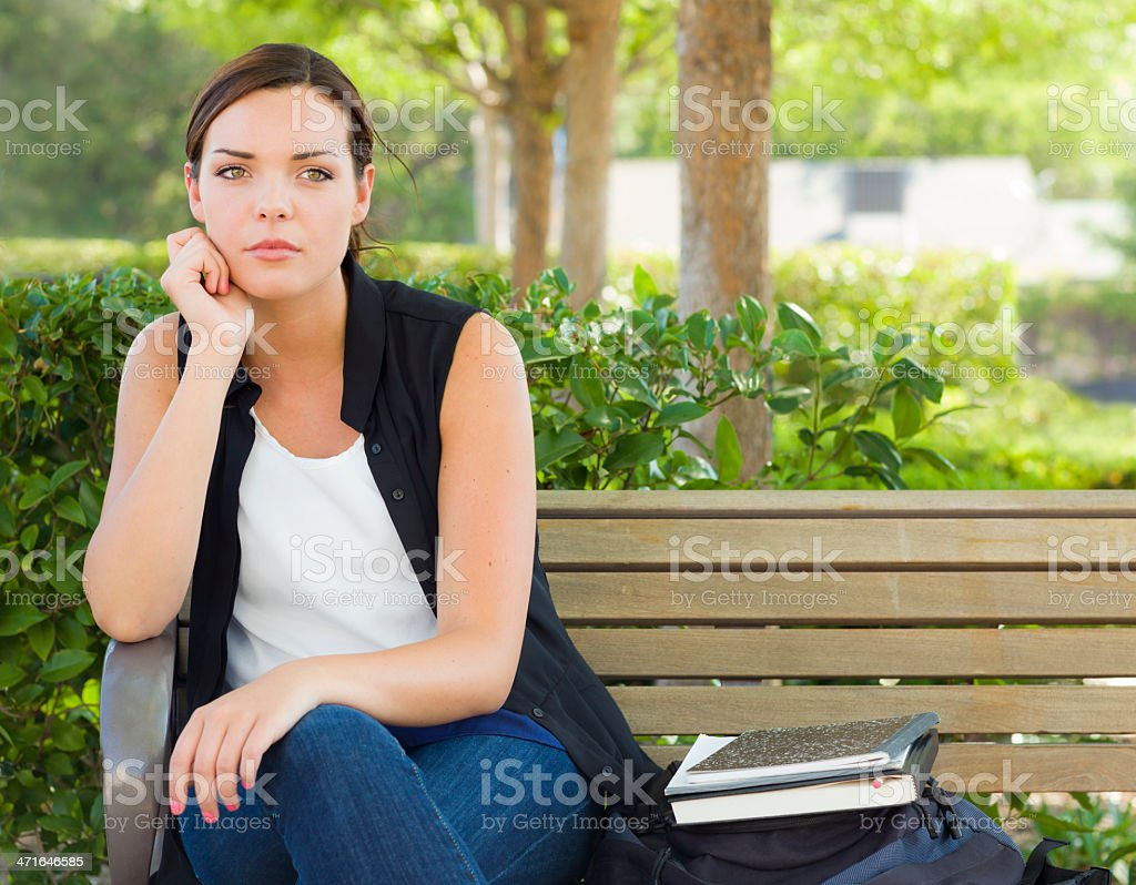 Melancholy Young Adult Woman Sitting on Bench Next to Books royalty-free stock photo