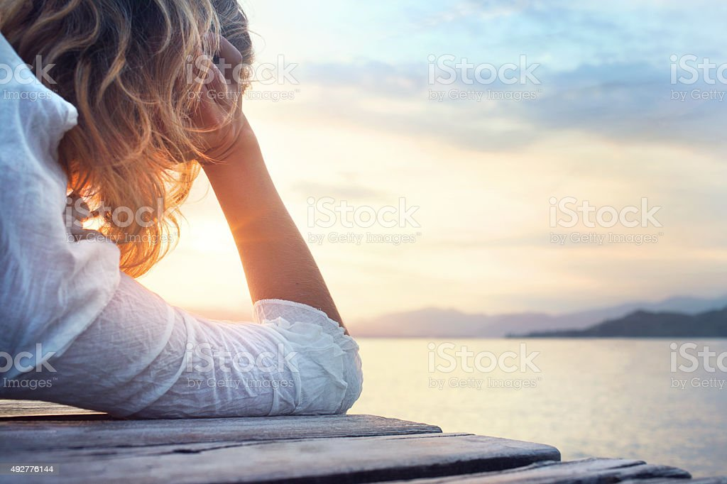 melancony woman observing the sunset stock photo
