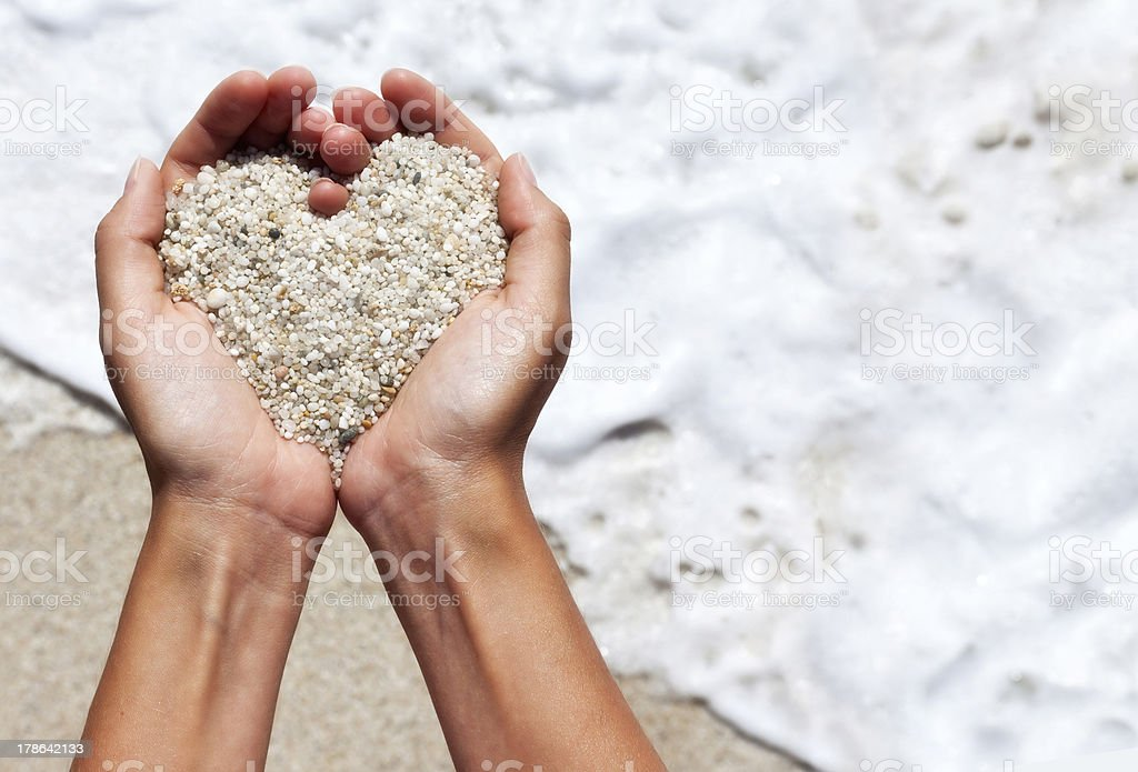 Mellow heart shaping female hands above beach stock photo