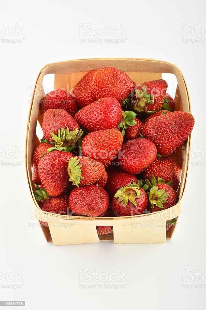 Mellow strawberries in wooden basket isolated on white royalty-free stock photo