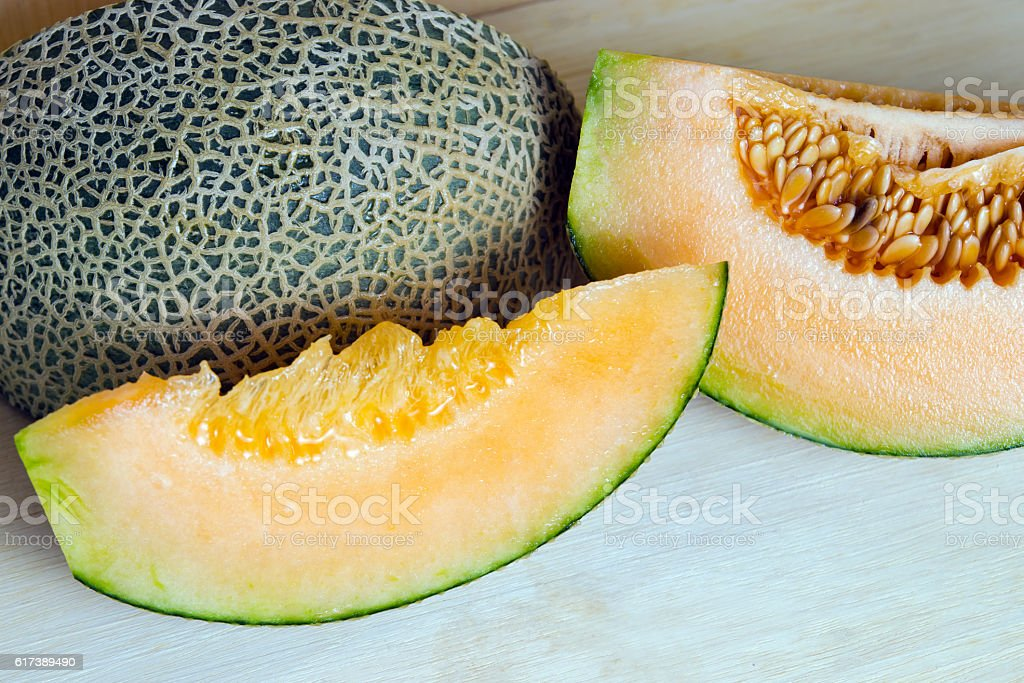 Melon or cantaloupe sliced on wooden board with seeds stock photo