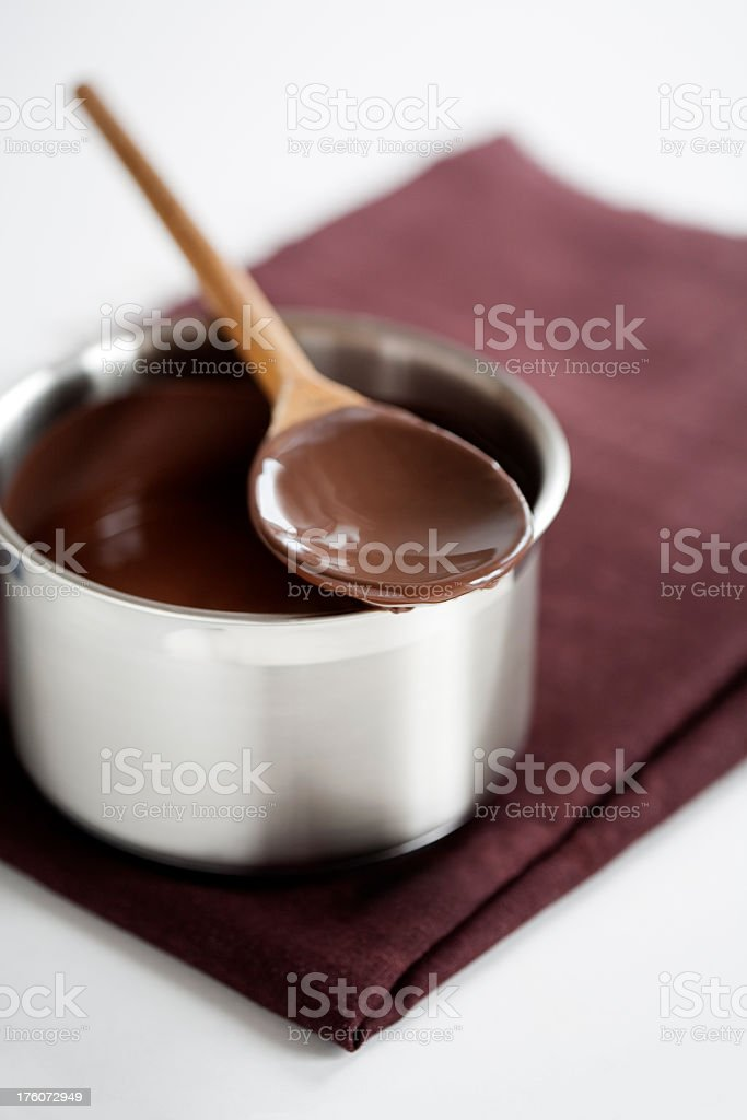 Melted chocolate in a silver bowl with a spoon royalty-free stock photo