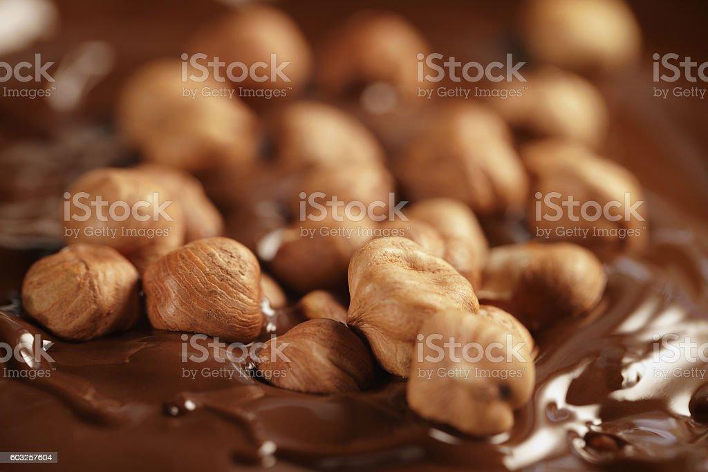 melted dark chocolate with hazelnuts, making chocolate bar stock photo