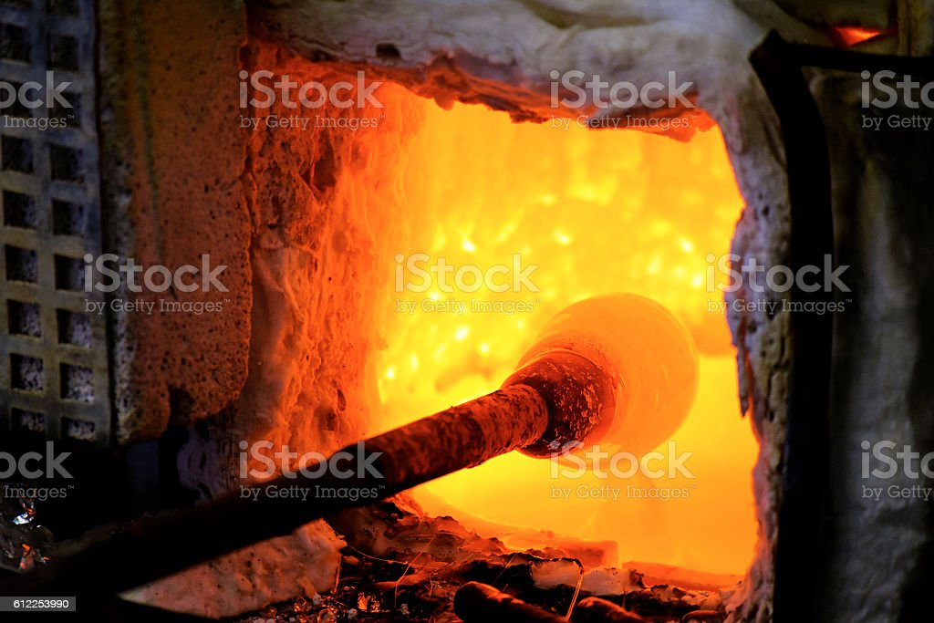 melted glass in a traditional glasblower oven stock photo