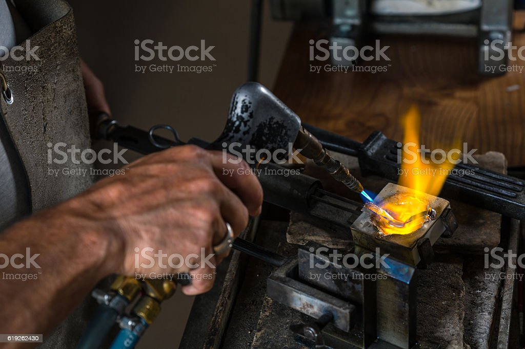 Melting a Silver Ingot in crucible with blowtorch stock photo