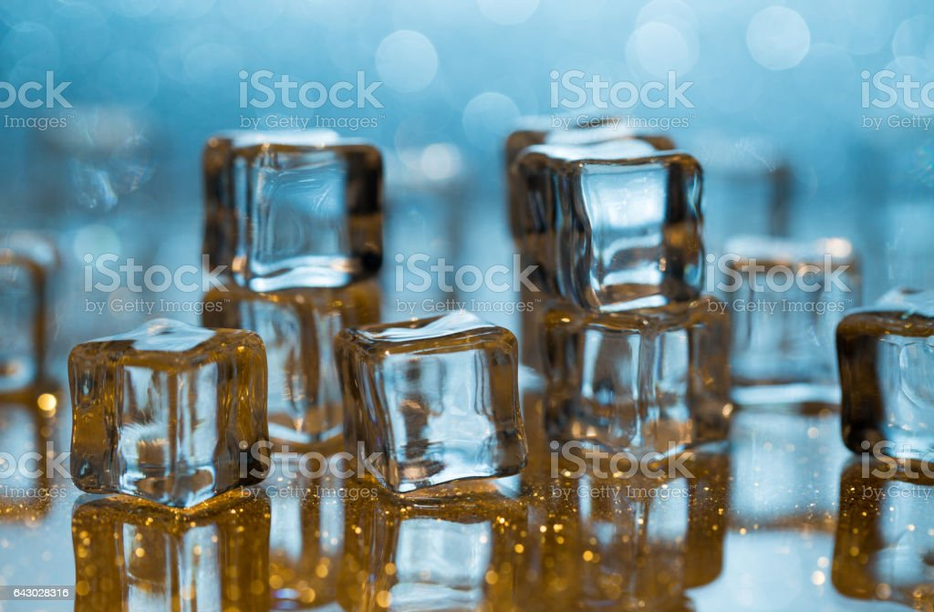 Melting ice cubes on glass table stock photo