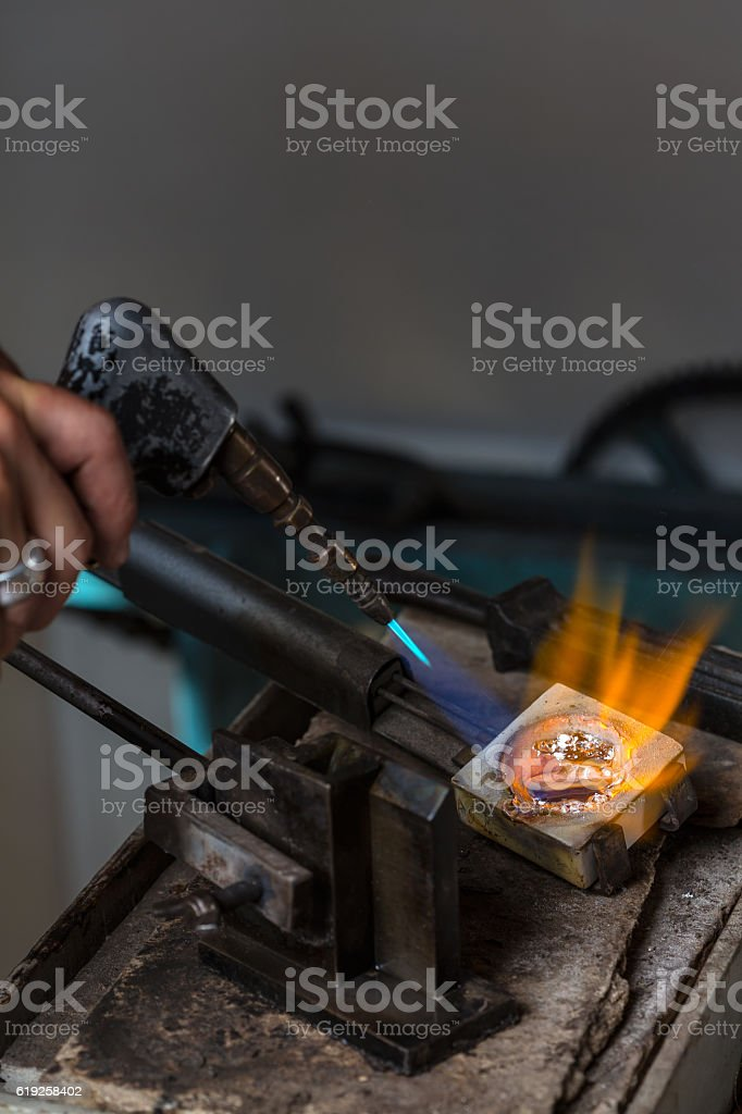 Melting Silver Grains in crucible with blowtorch stock photo