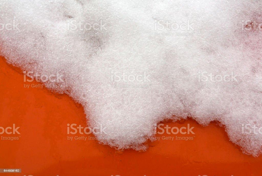 Melting snow on orange car surface stock photo