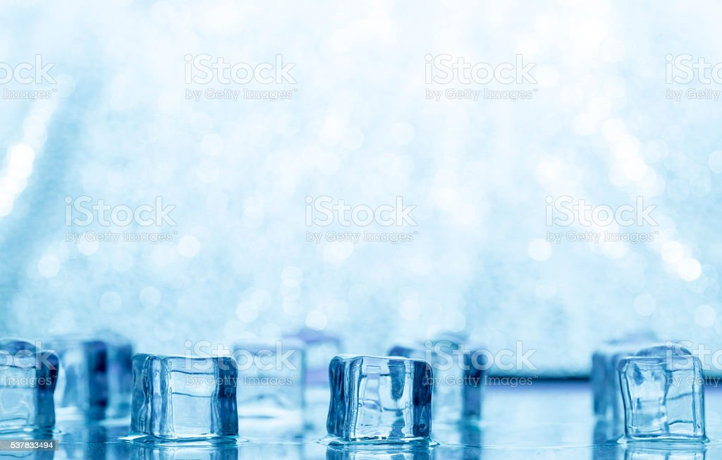 Melting transparent blue ice cubes on glass stock photo