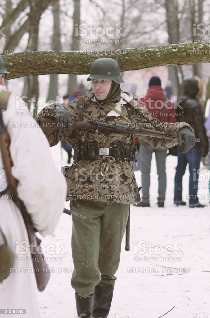 Member of military reconstruction in the form of a German soldier with a rifle. stock photo