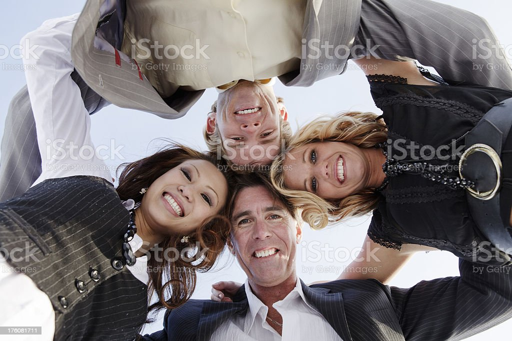 Members of a diverse team sticking their heads together royalty-free stock photo