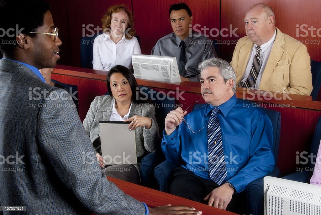 Members of diverse jury listening to an attorney in courtroom stock photo