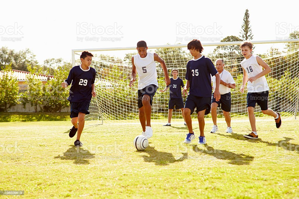 Members Of Male High School Soccer Playing Match stock photo