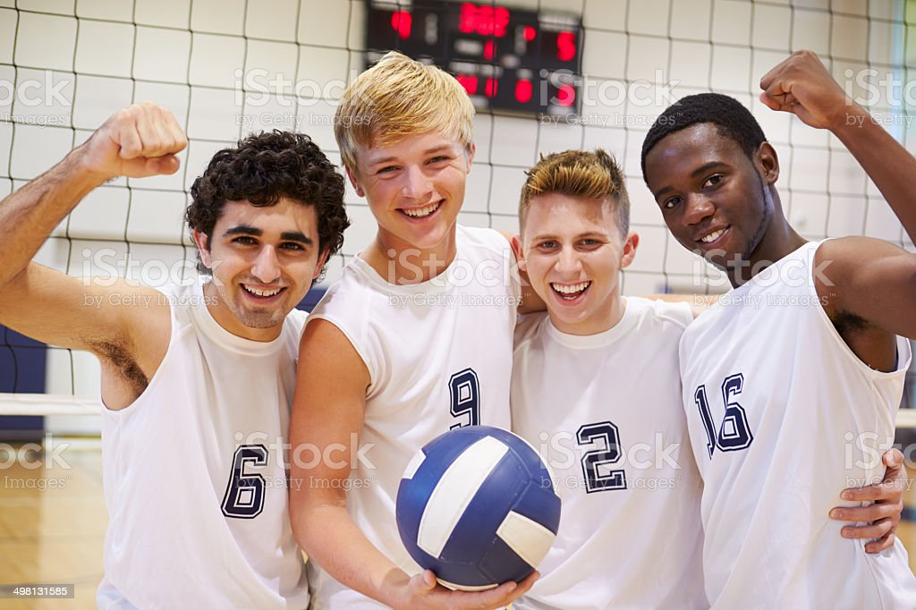 Members Of Male High School Volleyball Team Holding Ball Smiling