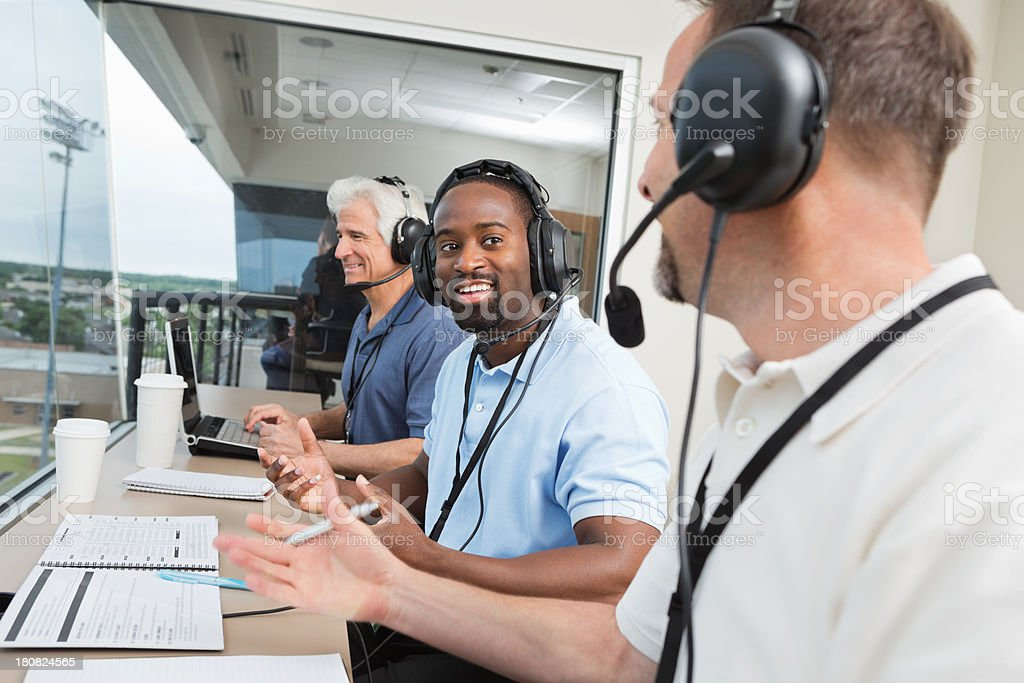 Members of media reporting on sports game in press box stock photo