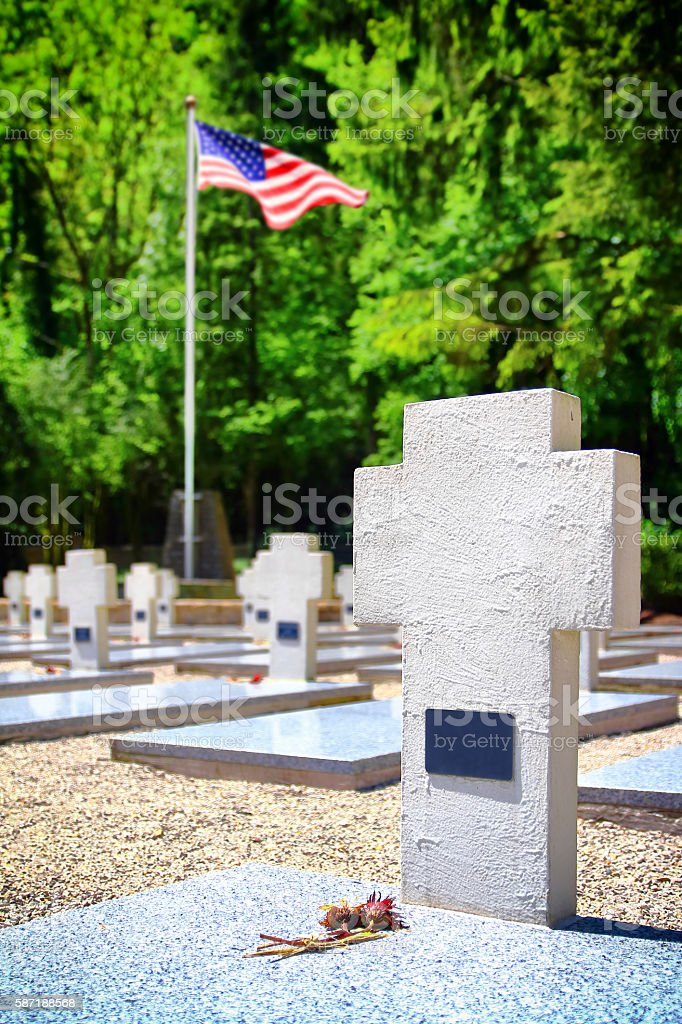 Memorial WWII cemetery gravestones with USA flag blurred in background stock photo