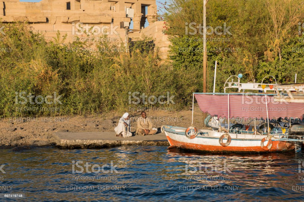 Men and a boat at the Temple of Philae, Aswan, Egypt. stock photo