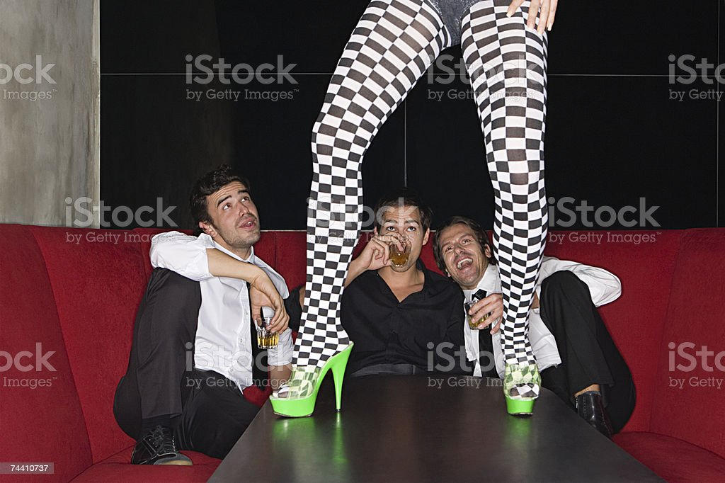 Men and legs of table dancer stock photo
