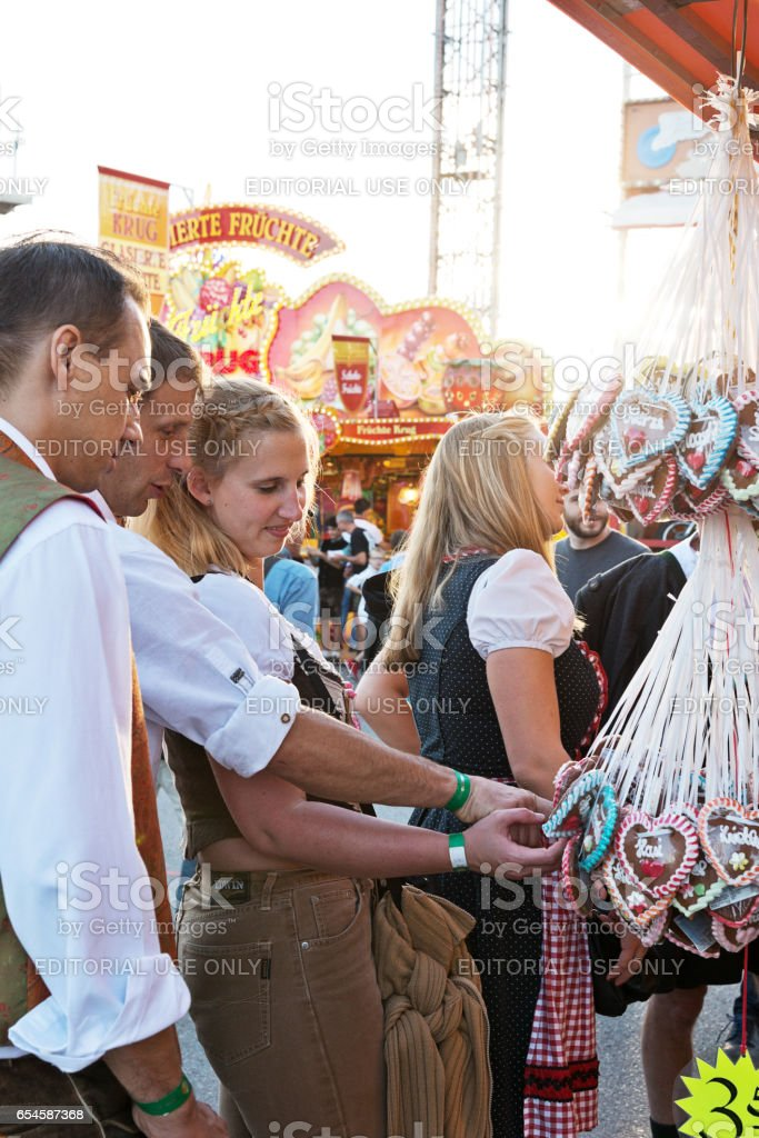 Men and woman choosing a gingerbread heart at Oktoberfest stock photo