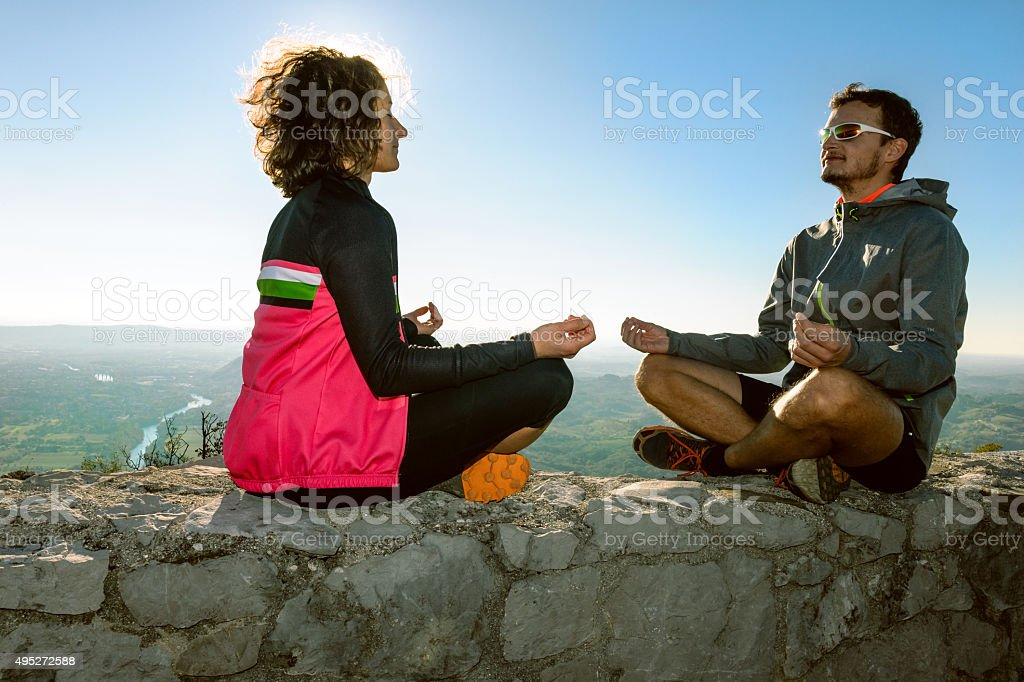 Men and woman sit meditate on the wall,Primorska,Slovenia stock photo
