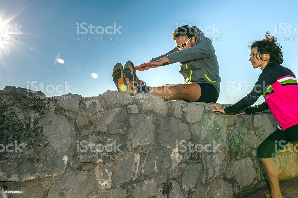 Men and woman sit stretching on the wall,Primorska,Slovenia stock photo