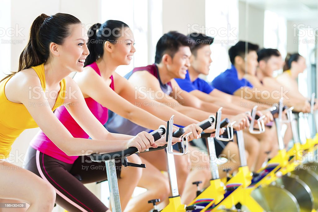 Men and women attend a spin class at a gym royalty-free stock photo