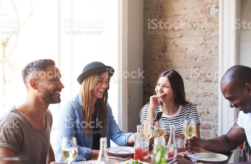 Men and women having a good time at dinner stock photo