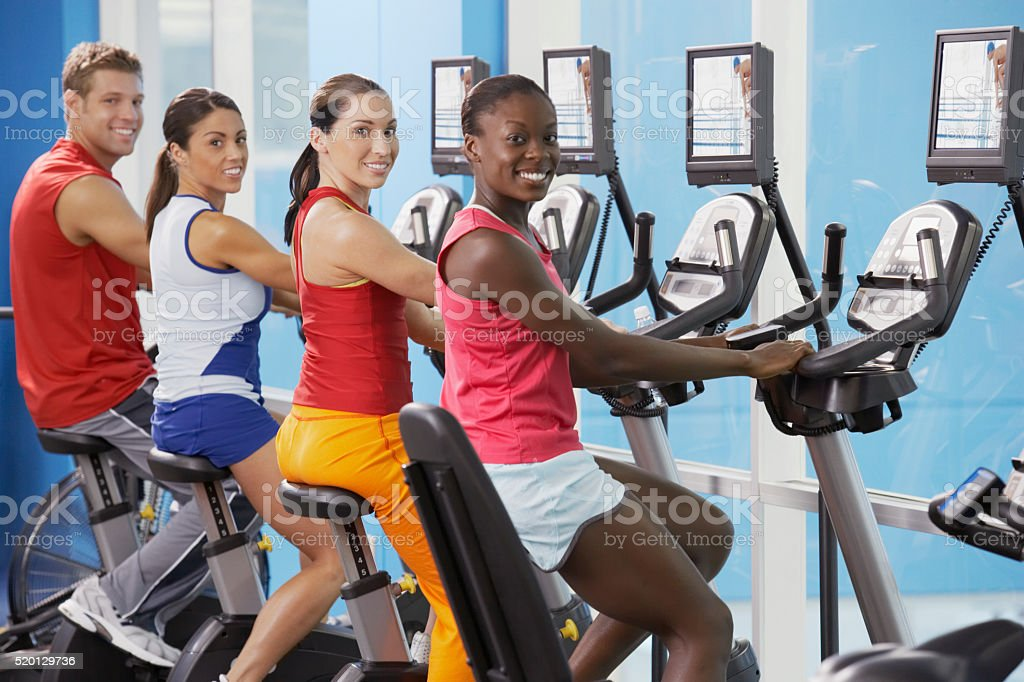 Men and women on cycling machines stock photo