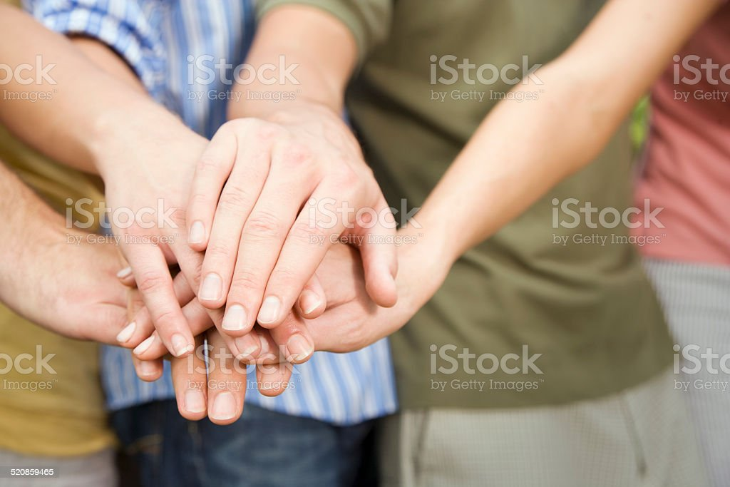 Men and Women Putting Their Hands Together as Team stock photo