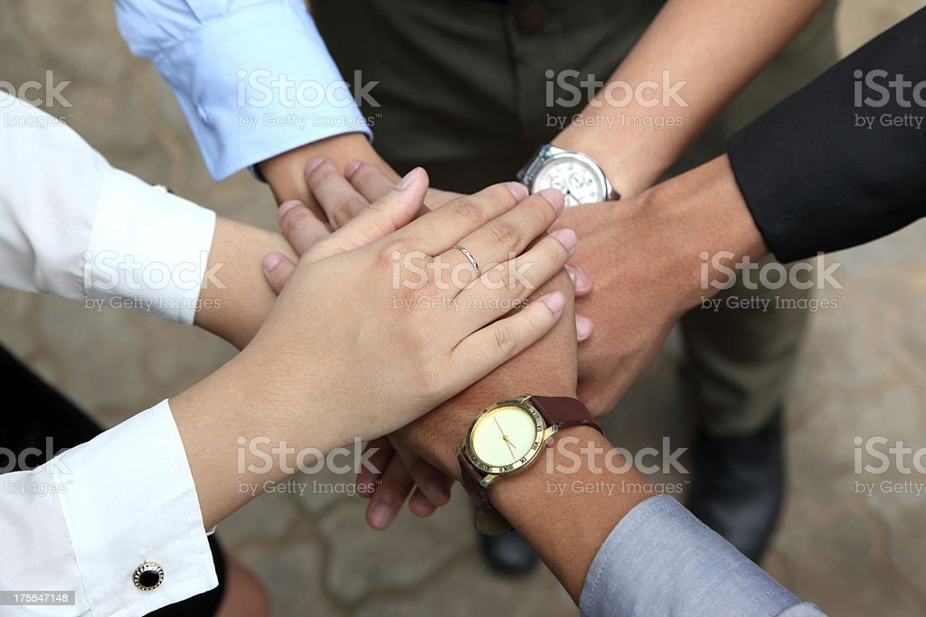 Men and women showing unity by putting their hands together stock photo