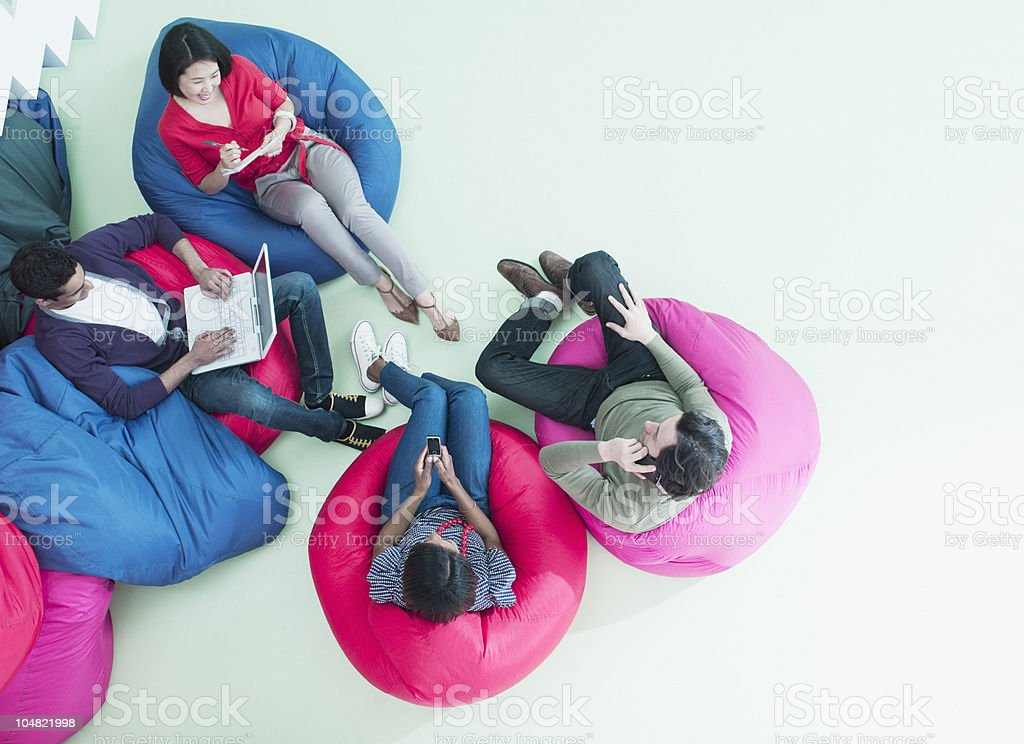 Men and women using laptop and cell phones in bean bag chairs stock photo