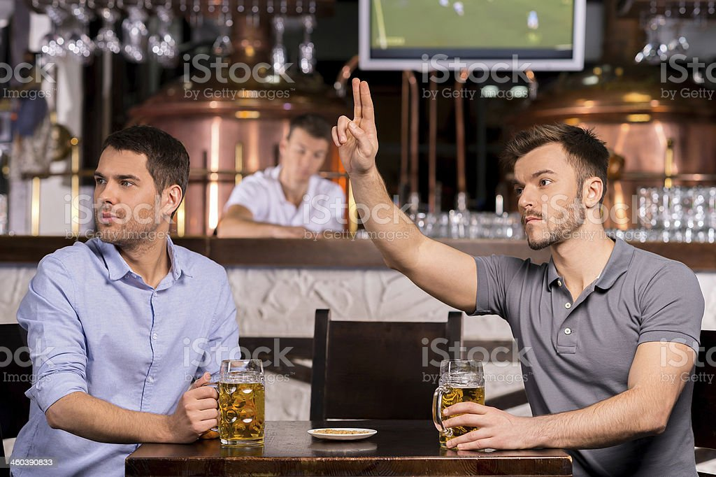 Men at a bar table with beers, one gesturing for service stock photo