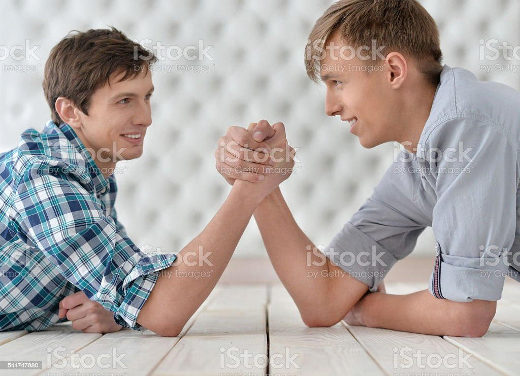 men  at the table and armwrestling stock photo