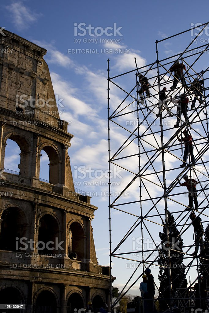 men at work on a scaffolding in front of Colosseum royalty-free stock photo