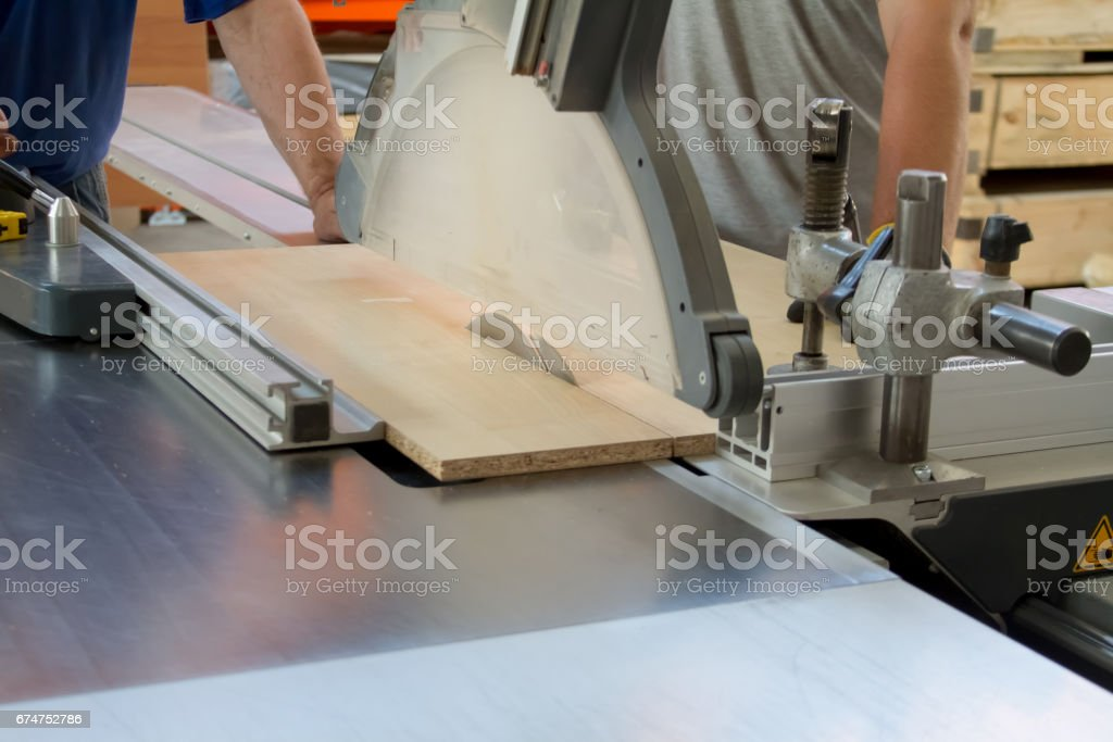 Men at work sawing wood. Circular saw. A machine which saws wood, particle Board and fiberboard. stock photo