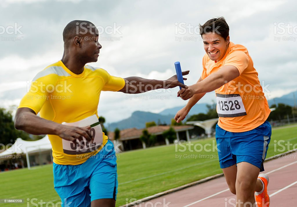 Men athletes in a relay race stock photo